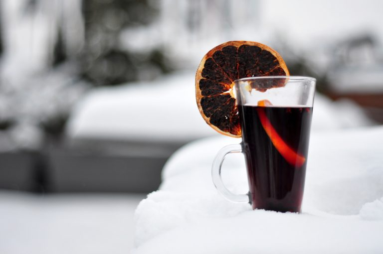Warm glass of red mulled wine dried oranges resting in the thick snow, by Art In Voyage