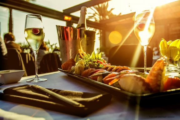 Luxury restaurant table with sushi dish , champagne and the sunset on Barcelona beach